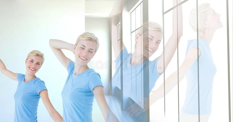 Mujer que ejercita yoga relajante por la ventana fotos de archivo