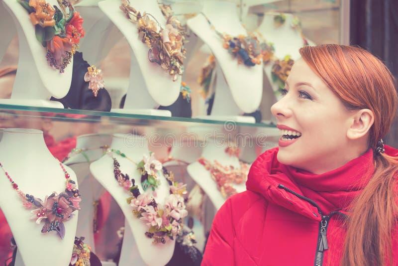 Mujer que elige el bijouterie en la ventana de la tienda en la isla de Italia Murano fotografía de archivo