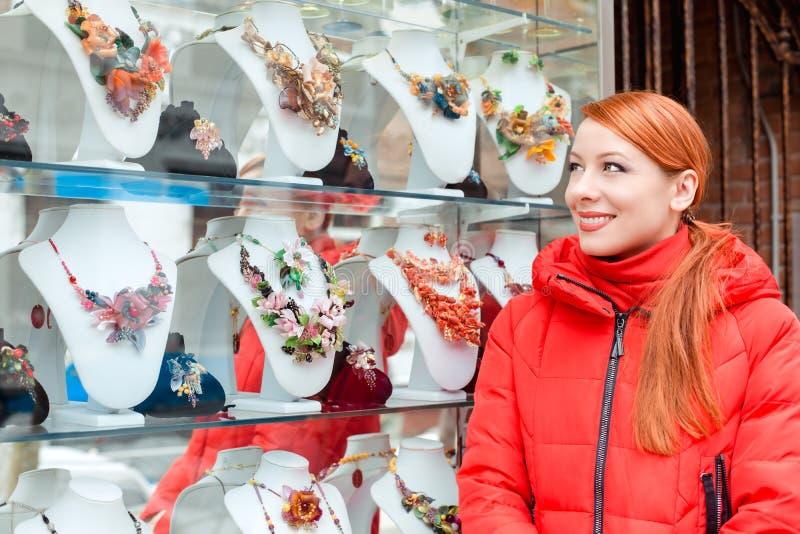 Mujer que elige el bijouterie en la ventana de la tienda en Italia Murano fotografía de archivo libre de regalías