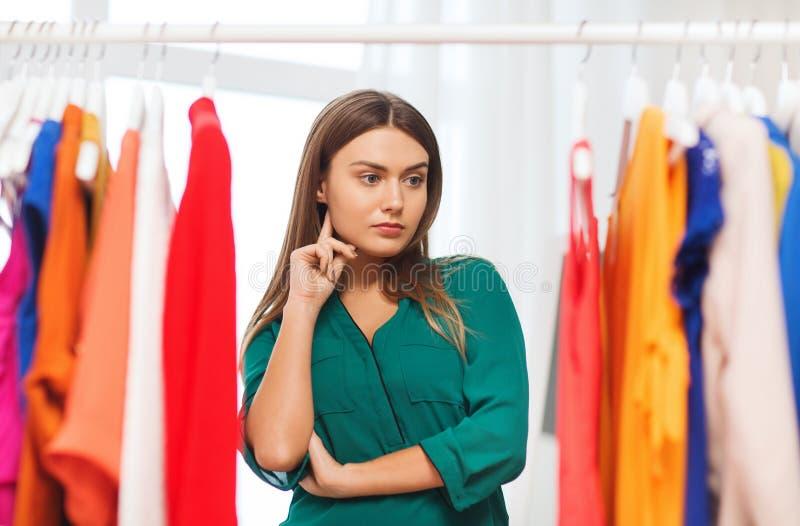 Mujer que elige el guardarropa de la ropa en casa imagen de archivo