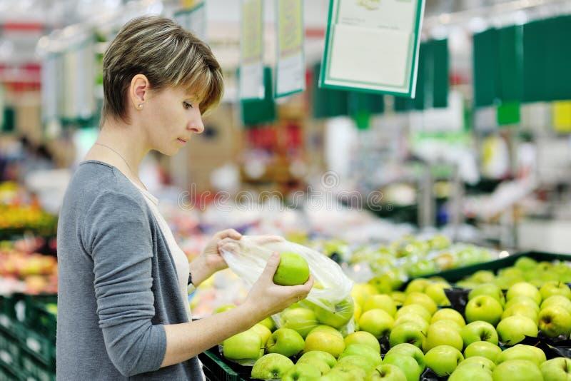 Mujer que elige la manzana en el supermercado de la fruta fotos de archivo