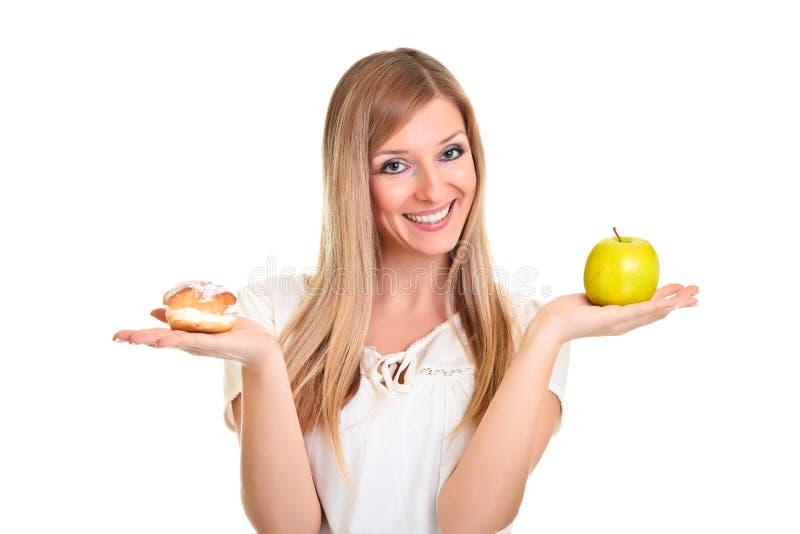 Mujer que elige la manzana sobre la galleta del soplo fotografía de archivo libre de regalías