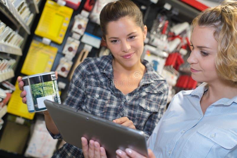 Mujer que elige la pintura del color durante compras del hardware en mejoras para el hogar imagenes de archivo