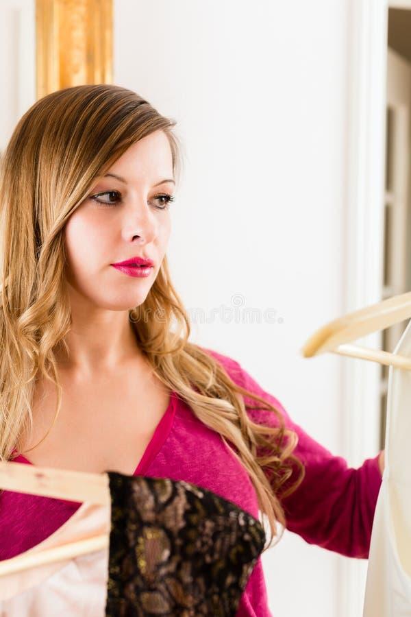 Mujer que elige la ropa para ella fotografía de archivo