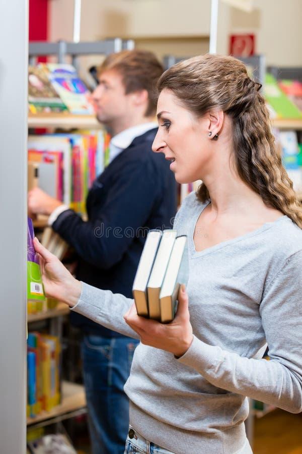 Mujer que elige los libros de estante en biblioteca foto de archivo