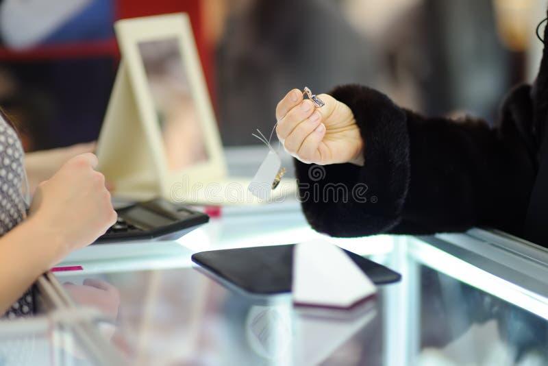 Mujer que elige los pendientes perfectos en un joyero, cierre encima de la foto foto de archivo libre de regalías