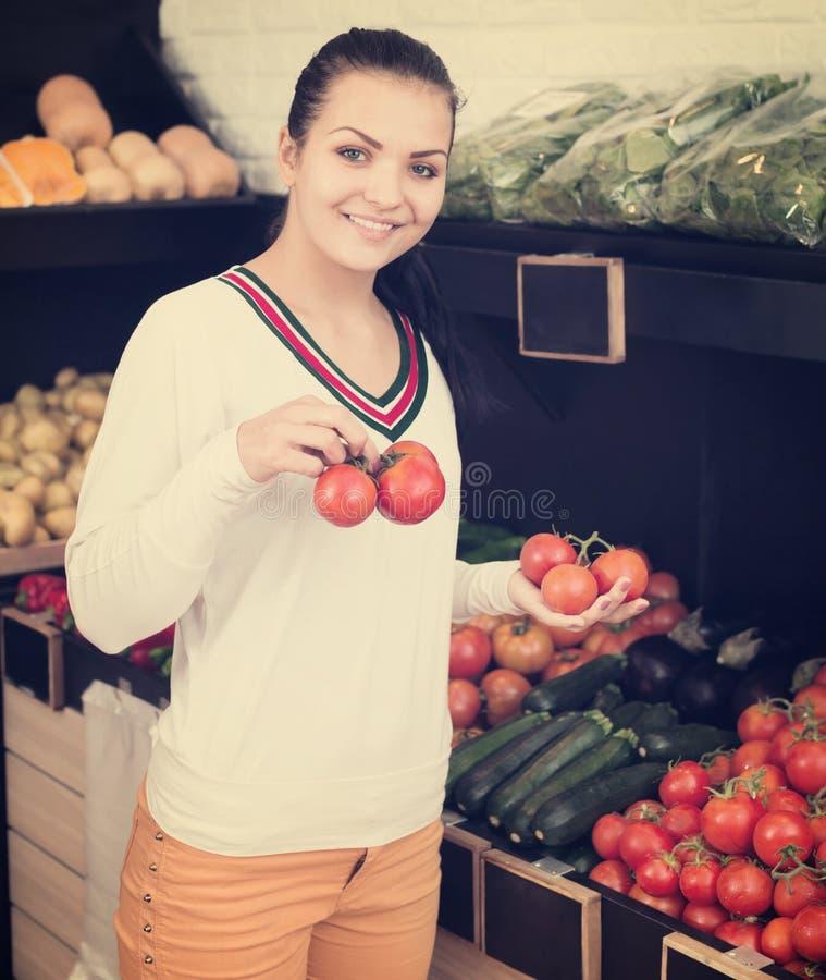 Mujer que elige los tomates en tienda de ultramarinos imagen de archivo
