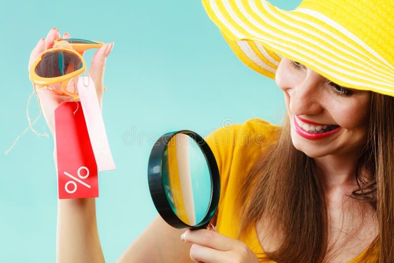 Mujer que elige los vidrios que buscan a través de la lupa fotos de archivo