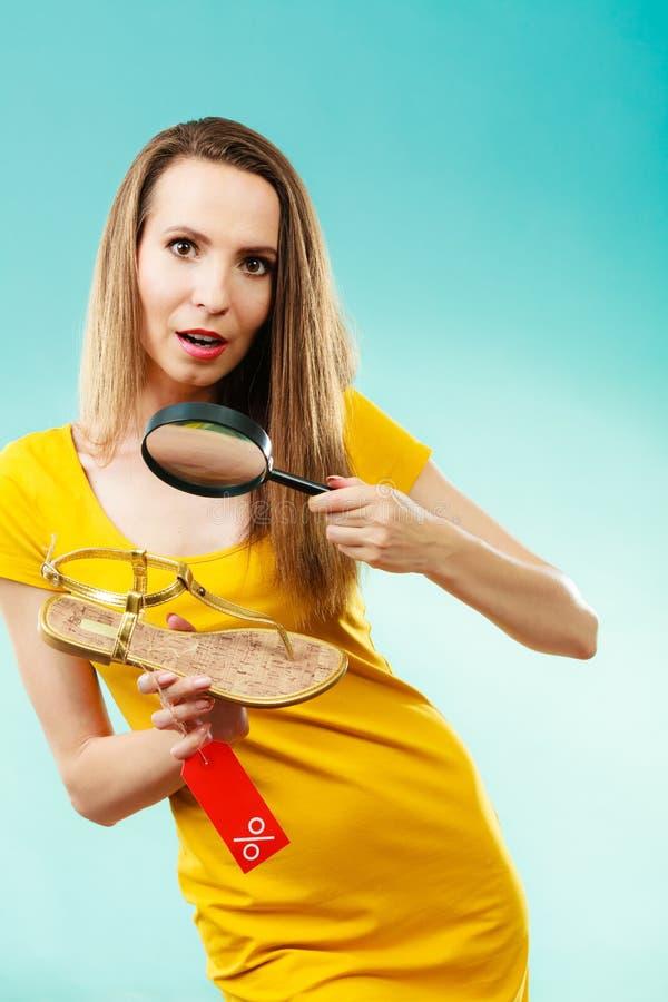Mujer que elige los zapatos que buscan a través de la lupa fotografía de archivo libre de regalías