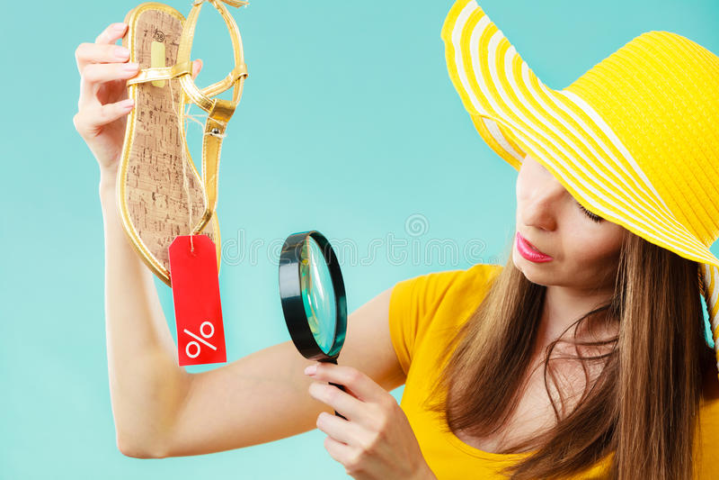 Mujer que elige los zapatos que buscan a través de la lupa imagen de archivo