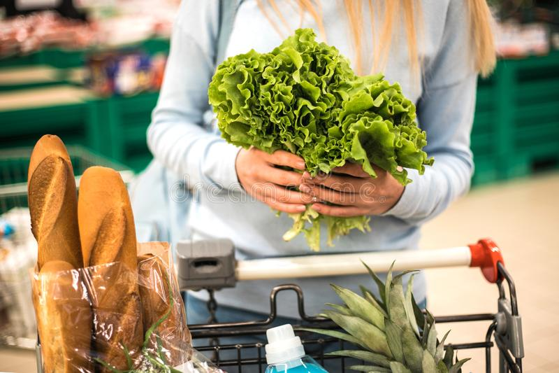 Mujer que elige verduras frondosas verdes en ultramarinos foto de archivo libre de regalías