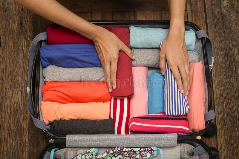 Mujer que embala un equipaje para un nuevo viaje foto de archivo