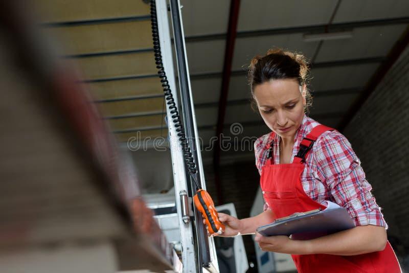 Mujer que empuja el botón rojo en fábrica imagen de archivo libre de regalías