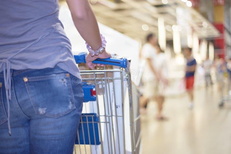 Mujer que empuja el carro de la compra en alameda de compras foto de archivo
