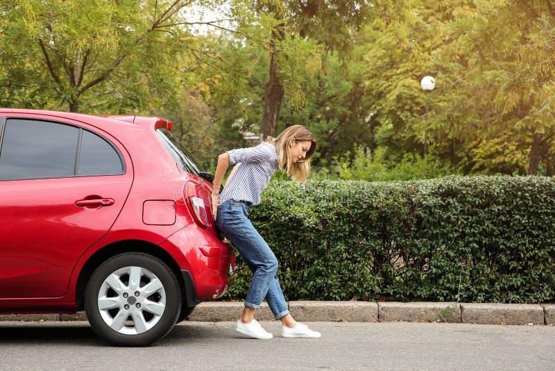 Mujer que empuja el coche quebrado en el camino fotos de archivo