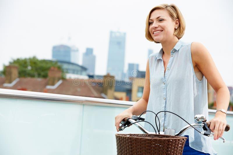 Mujer que empuja la bici con horizonte de la ciudad en fondo imagen de archivo libre de regalías