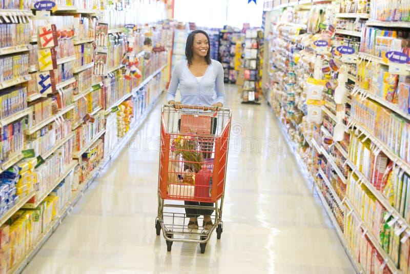 Mujer que empuja la carretilla a lo largo del pasillo del supermercado imagenes de archivo