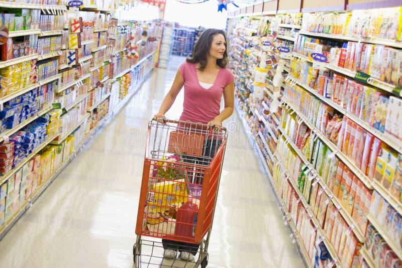 Mujer que empuja la carretilla a lo largo del pasillo del supermercado imagen de archivo