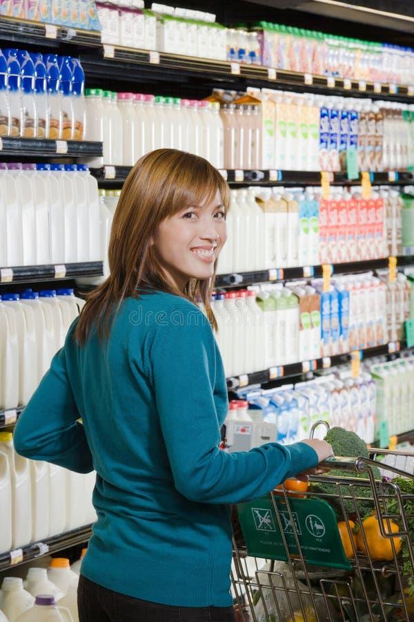 Mujer que empuja una carretilla de las compras imagen de archivo