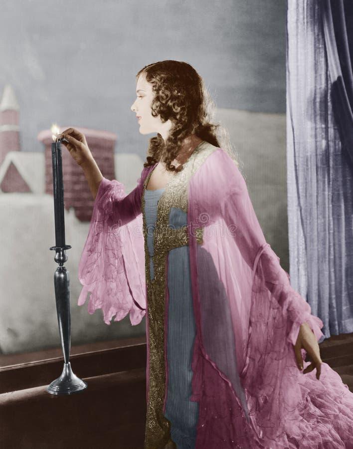 Mujer que enciende la vela el la tarde del invierno (todas las personas representadas no son vivas más largo y ningún estado exis foto de archivo
