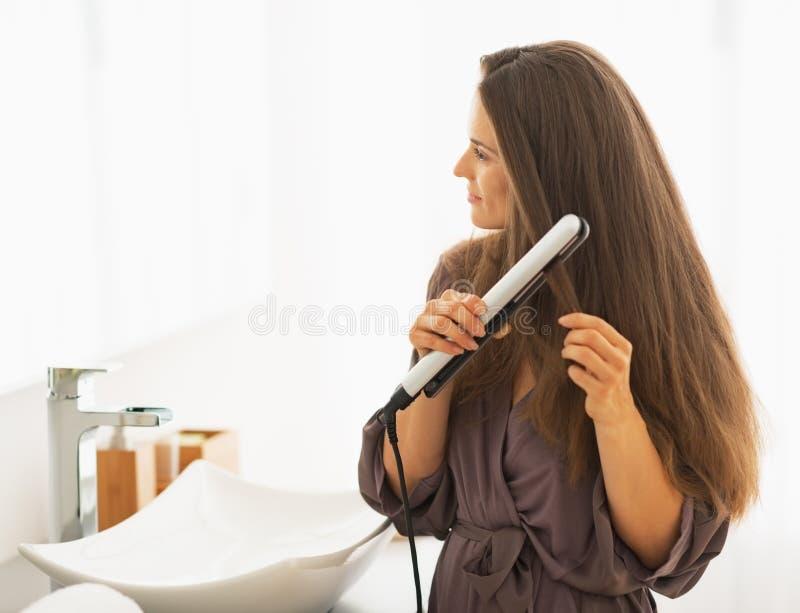 Mujer que endereza el pelo con la enderezadora imagenes de archivo