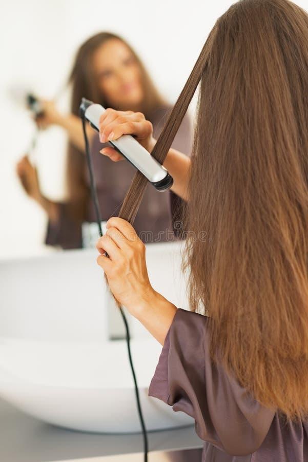 Mujer que endereza el pelo con la enderezadora foto de archivo libre de regalías