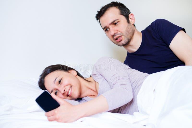 Mujer que engaña y que charla en el teléfono móvil imagen de archivo