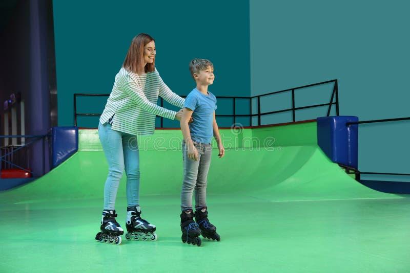 Mujer que enseña a su patinaje sobre ruedas del hijo en la pista fotografía de archivo libre de regalías