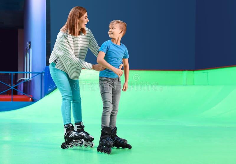 Mujer que enseña a su patinaje sobre ruedas del hijo en la pista imagen de archivo