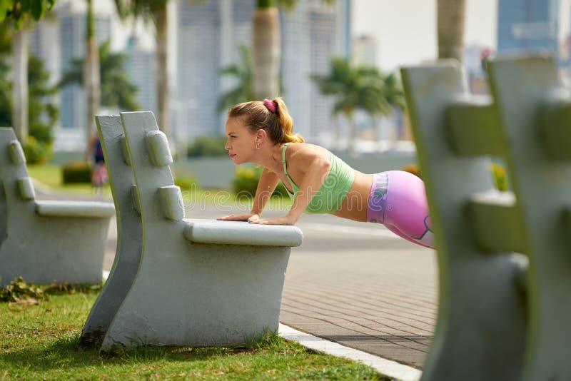 Mujer que entrena a Pectorals que hace flexiones de brazos en la calle Bench-3 imagenes de archivo