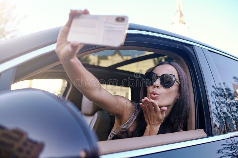 Mujer que envía beso que vuela mientras que toma el selfie en smartphone imagenes de archivo