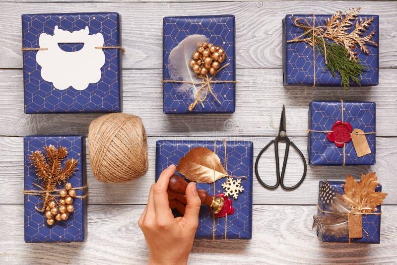 Mujer que envuelve regalos de Navidad sobre fondo de madera imágenes de archivo libres de regalías