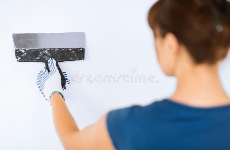 Mujer que enyesa la pared con la paleta fotos de archivo