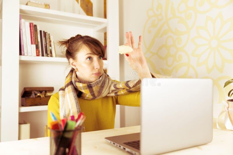Mujer que es juguetona en el trabajo, mirando el bocado sano fotos de archivo libres de regalías