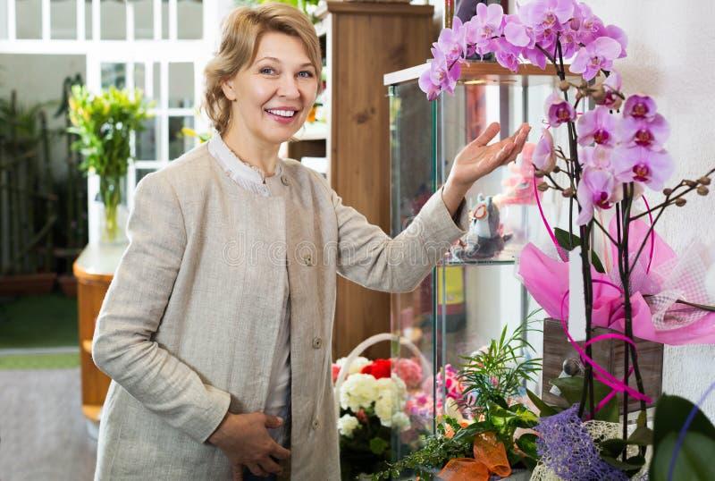 Mujer que escoge la flor en conserva del phalaenopsis foto de archivo