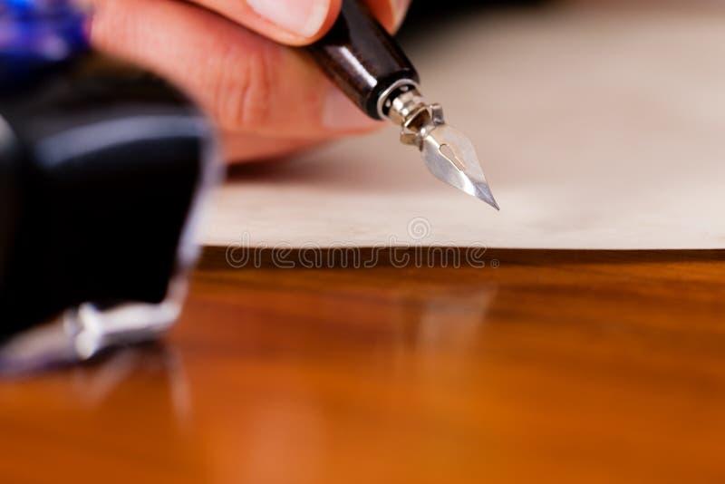 Mujer que escribe una letra con la pluma y la tinta imagenes de archivo