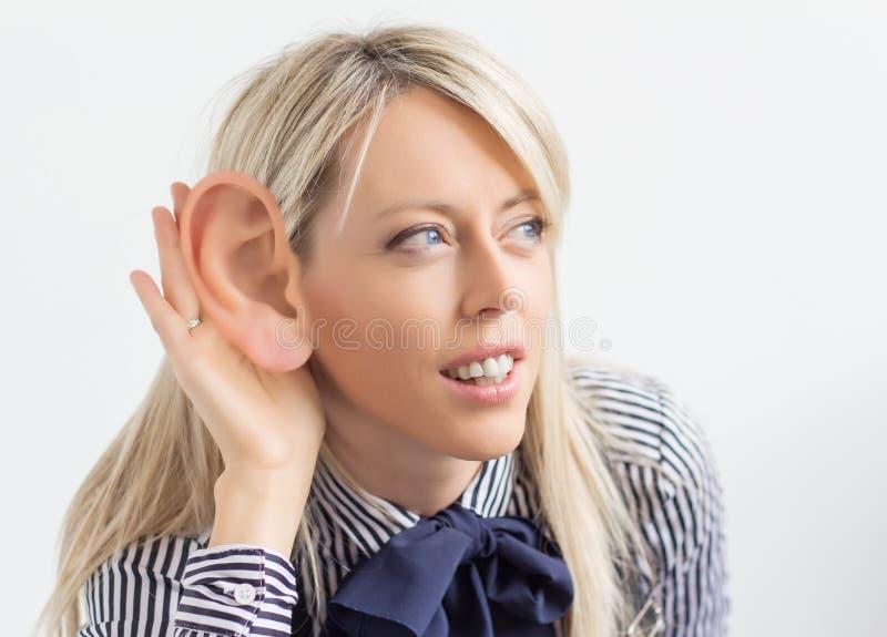 Mujer que escucha con el oído ridículo grande fotos de archivo libres de regalías