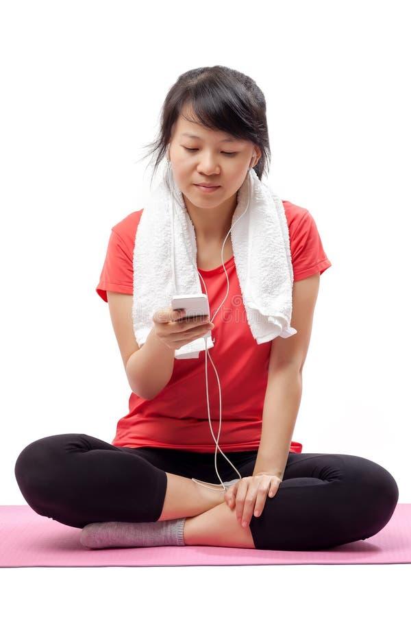 Mujer que escucha la música en equipo del ejercicio fotografía de archivo
