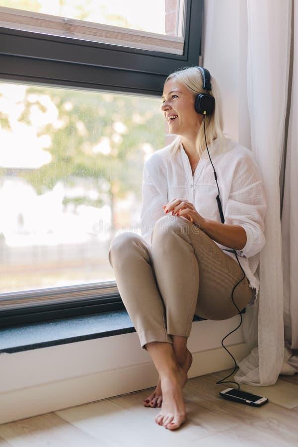 Mujer que escucha la música en un travesaño de la ventana imagen de archivo