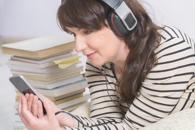Mujer que escucha un audiolibro fotografía de archivo libre de regalías