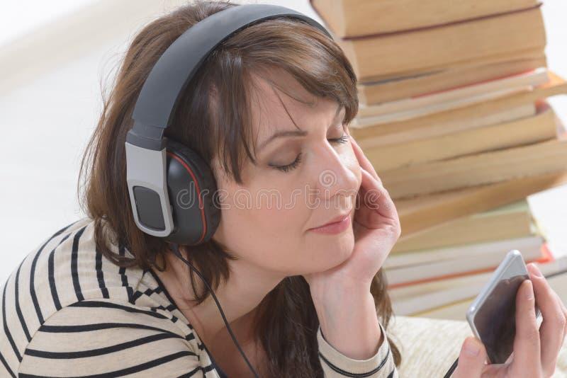 Mujer que escucha un audiolibro fotos de archivo libres de regalías