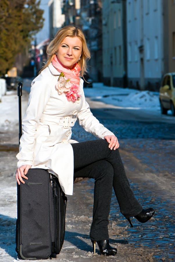 Mujer que espera en el camino con su bagaje imagenes de archivo