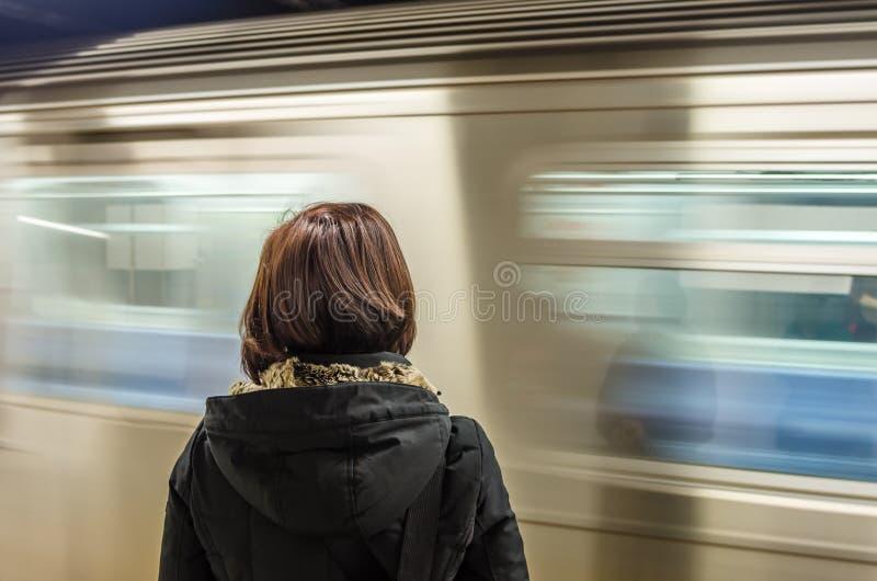 Mujer que espera en una estación de metro con un tren en el movimiento imagen de archivo libre de regalías