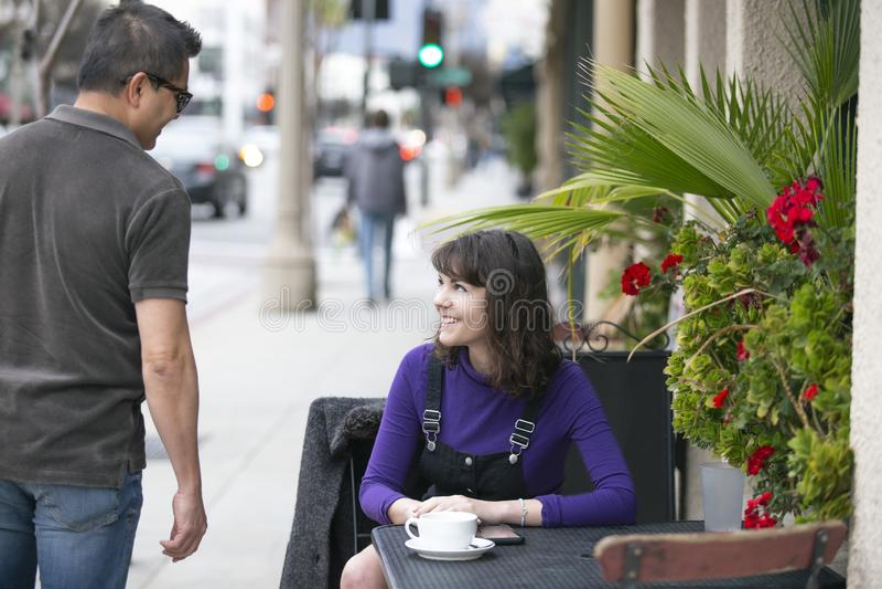 Mujer que espera a un amigo en un café local de la acera imágenes de archivo libres de regalías