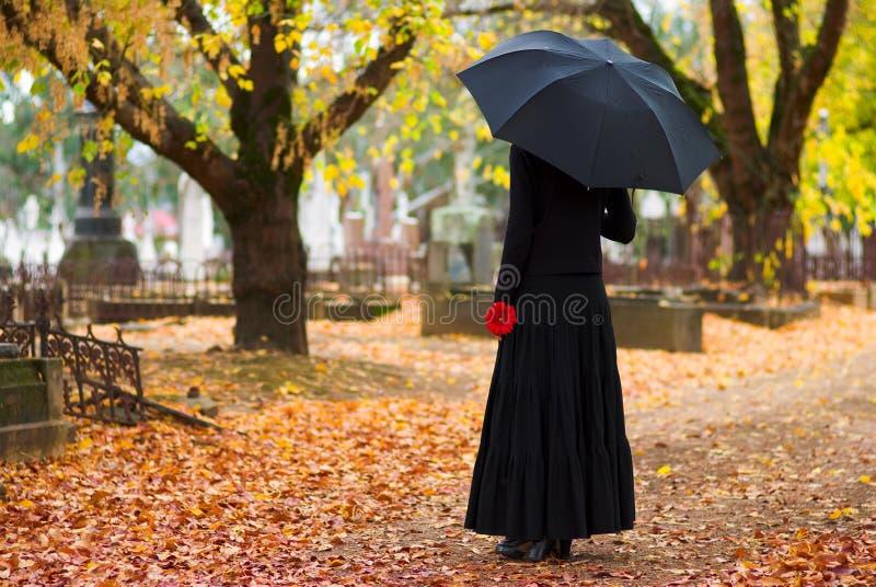 Mujer que está de luto en el cementerio fotos de archivo