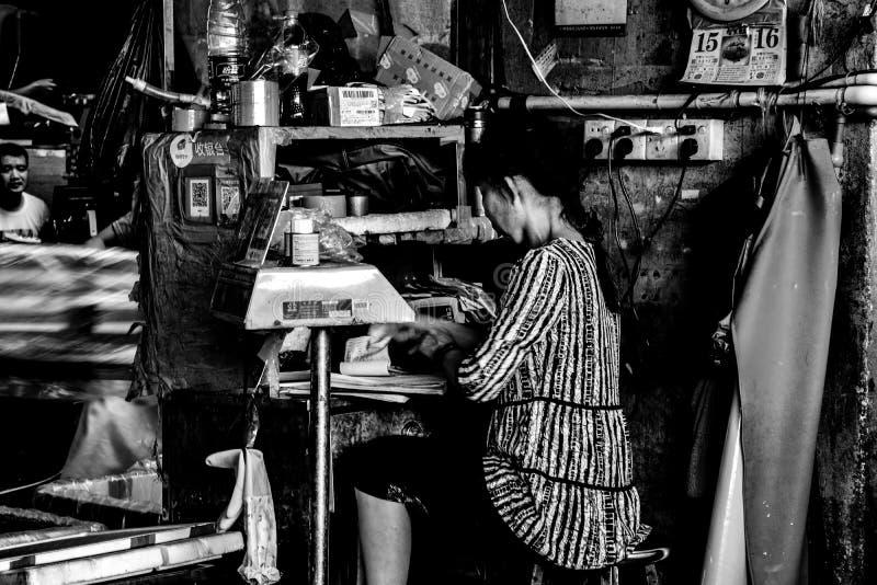 Mujer que está en el borde de la carretera viejo que computa en el distrito de Liwan, Guangzhou, China fotos de archivo libres de regalías