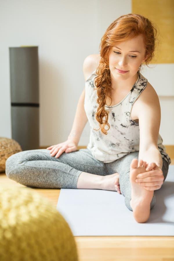 Mujer que estira durante clase de la yoga imagen de archivo libre de regalías