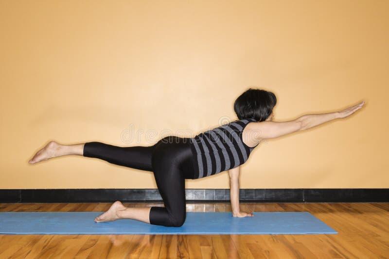 Mujer que estira en actitud de la yoga fotos de archivo