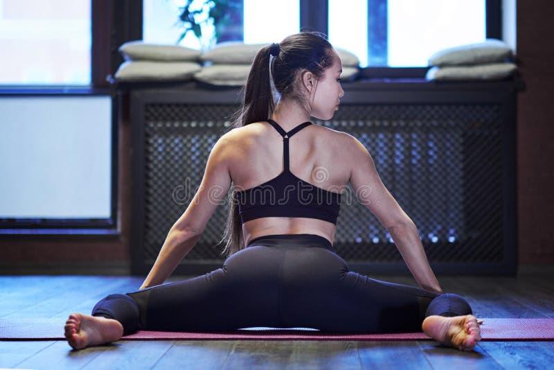 Mujer que estira en el piso en el estudio oscuro la muchacha asiática joven estira la opinión interna del muslo de la parte pos foto de archivo