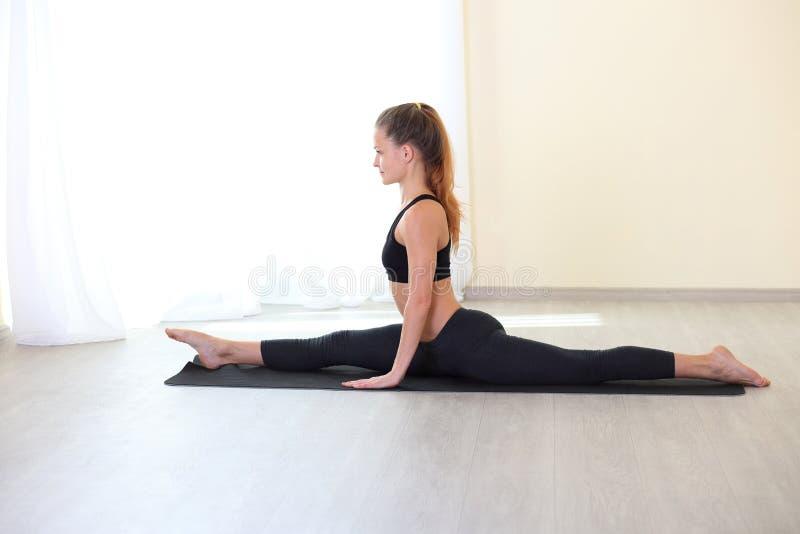 Mujer que estira las piernas en la posición de las fracturas en sitio brillante imagenes de archivo